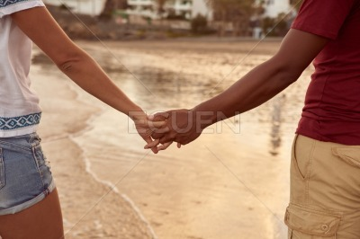 Intertwined fingers with reflections in water