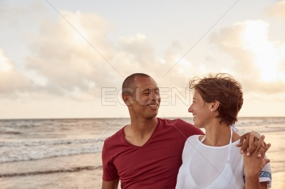 Joyfully laughing couple on beach shore