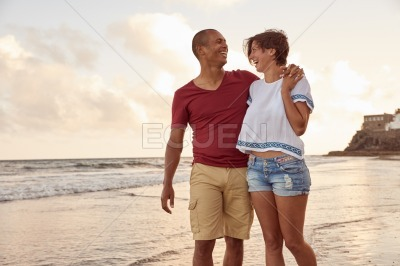 Laughing couple in the breaking waves