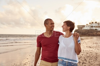 Laughing couple strolling on the beachfront