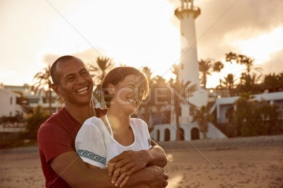 Laughing happy couple with a lighthouse