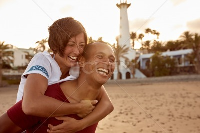 Laughing loving piggy back riding couple