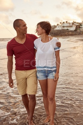 Loving adult couple chatting on beach