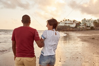 Playful lovers strolling on the beach