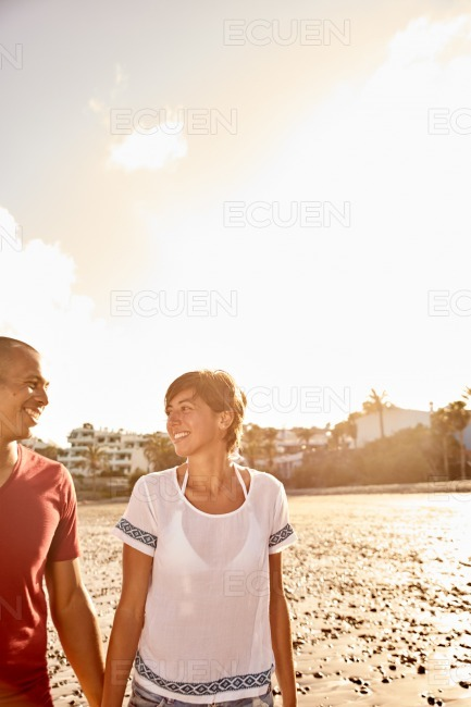 Couple strolling beach while holding hands stock photo