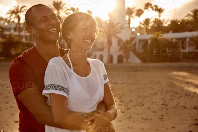 Embracing adult couple laughing with love stock photo