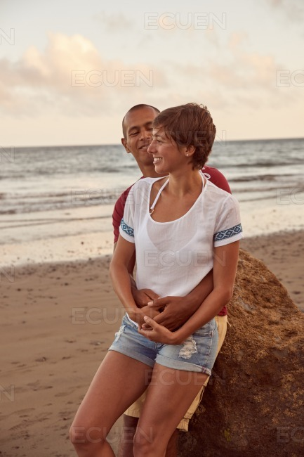 Embracing adult lovers on the beach stock photo