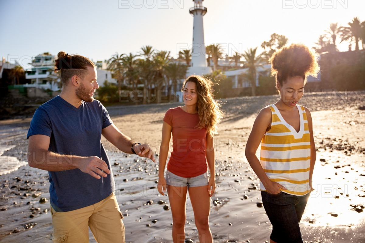 Cheerful friends walking in the waves stock photo
