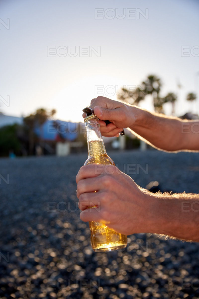 Male hands opening a sundowner beer stock photo