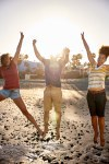 Friends jumping joyously on the beach