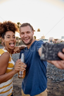 Funny friends taking selfies on beach