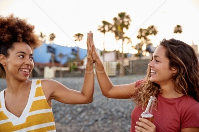 Girl friends high fiving each other