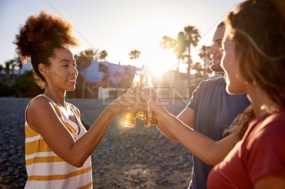Happy friends clinking beers on beach