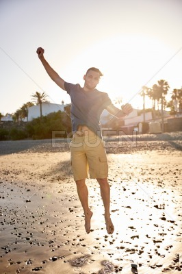 Happy young man jumping on beach