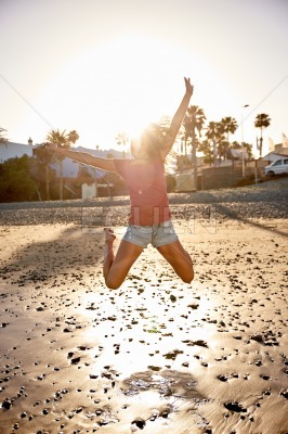 Joyful young woman jumping on beach