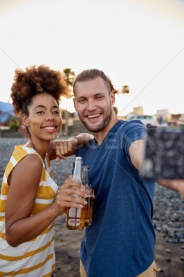 Laughing friends taking selfies on beach