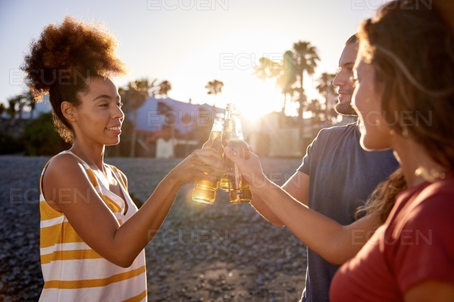 Happy friends clinking beers on beach stock photo