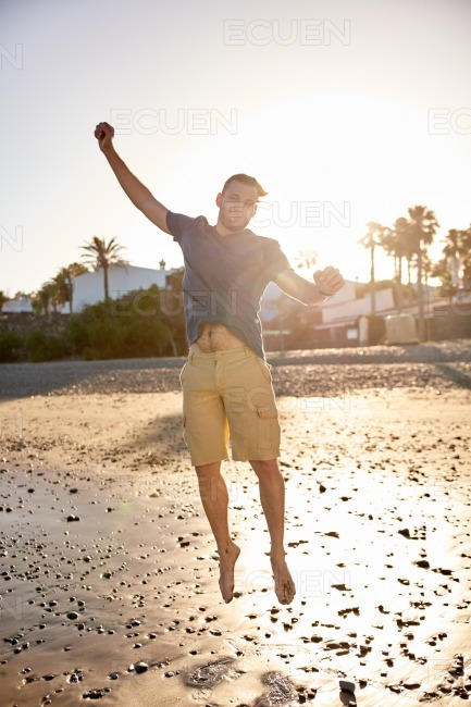 Happy young man jumping on beach stock photo