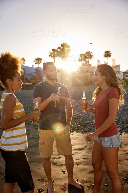 Joyful friends drinking beer on beach stock photo