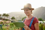Smiling girl with ipad and hat