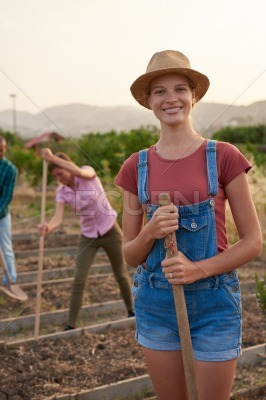 Friendly female farmer posing with rake