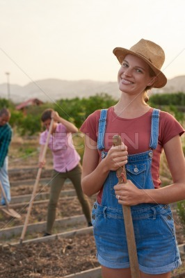 Happy female farmer posing with spade