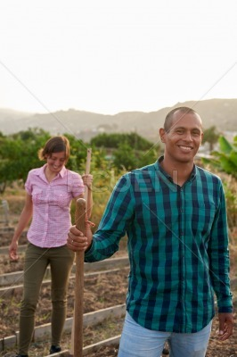 Happy young farmers in vegetable patch