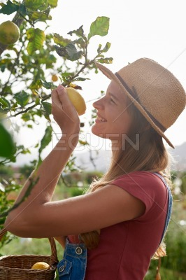 Happy young woman smelling a lemon