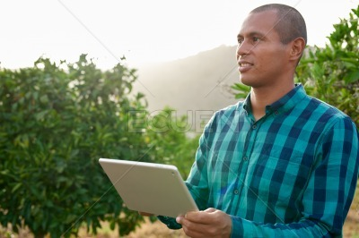 Male with tablet looking into distance