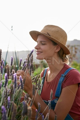 Pretty young farmer smelling her lavender