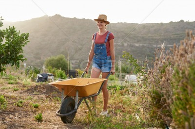 Smiling young woman pushing a wheelbarrow