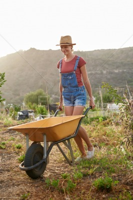 Smiling young woman pushing yellow wheelbarrow