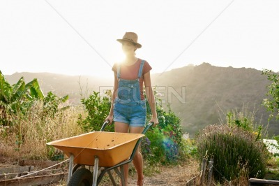 Woman with dungarees pushing a wheelbarrow
