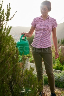 Young brunette farmer with watering can