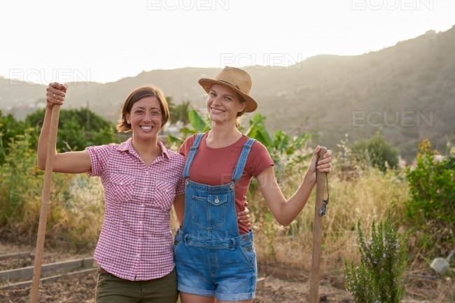Happy female farmers posing with shovels stock photo