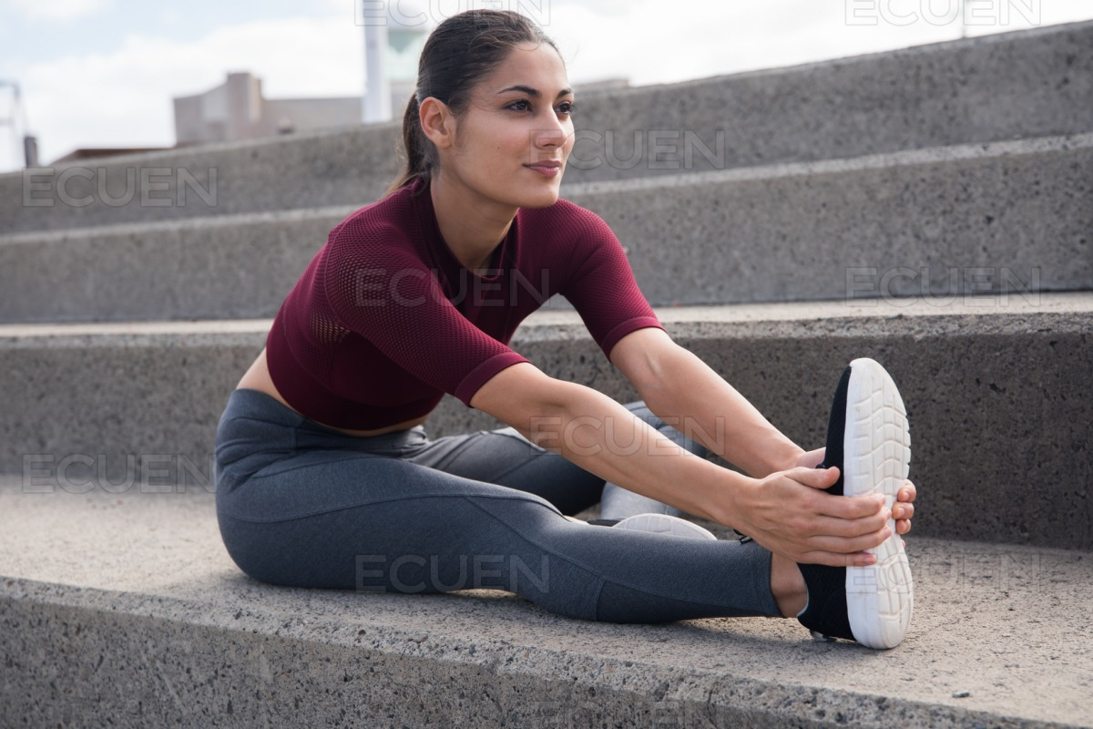 Attractive brunette doing exercises on stairs stock photo