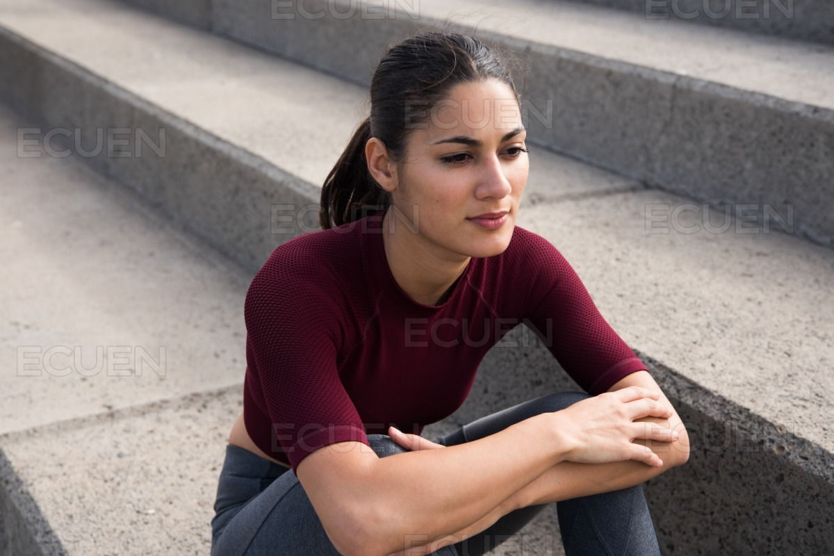 Attractive young woman sitting on stairs stock photo
