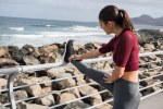 Pretty brunette excercising at the sea side
