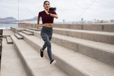 Attractive girl with brown hair running on stairs