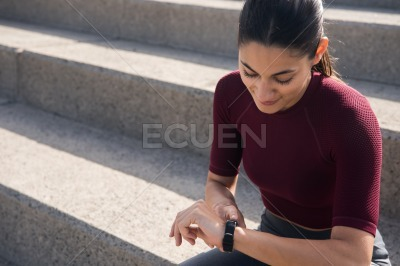 Attractive woman on stairs looking at watch