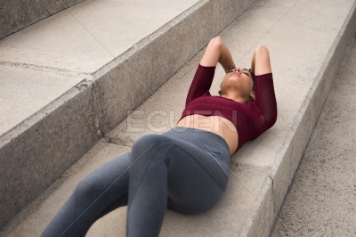 Fit young brunette lying on stairs