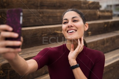 Pretty brunette taking a selfie on the stairs