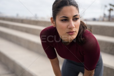 Pretty sporty brunette resting on stairs