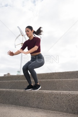 Pretty young brunette exercising on stairs