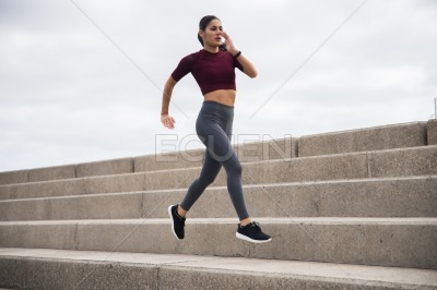 Pretty young brunette running on stairs
