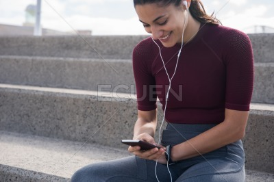 Smiling young woman with phone and ear phones