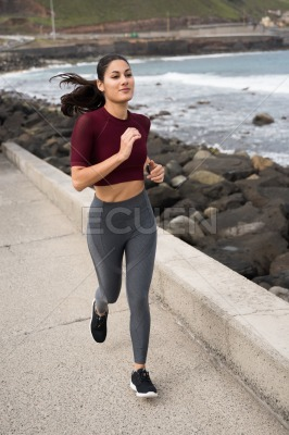 Sporty brunette running on the promenade