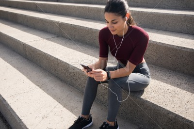 Sporty brunette sitting on stairs looking at phone