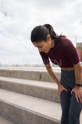 Sporty pretty woman with hands on knees