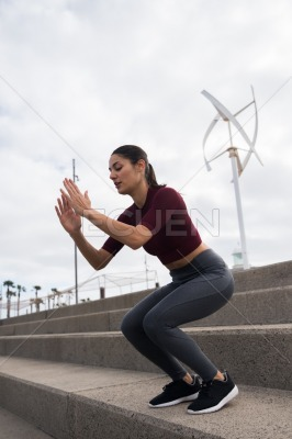 Sporty young brunette doing fitness on stairs